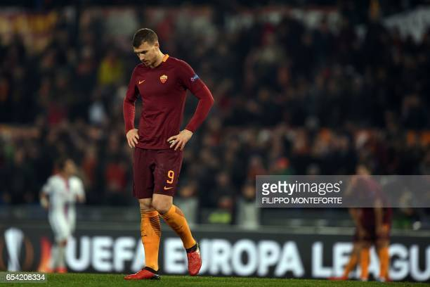Roma's Serbian forward Edin Dzeko reacts during the qualifying UEFA Europa League match AS Roma versus Lyon at Rome's Olympic stadium on March 16...
