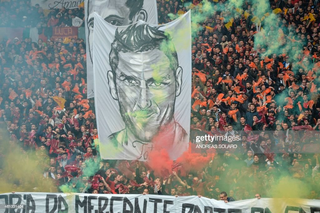 AS Roma's supporters deploy a giant portrait of captain Francesco Totti before the Italian football match AS Roma vs Lazio on January 11, 2015 at Rome's Olympic stadium. AFP PHOTO / ANDREAS SOLARO / AFP PHOTO / Andreas SOLARO
