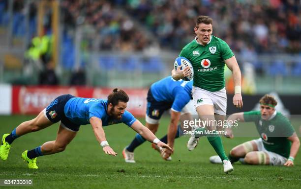 Rome Italy 11 February 2017 Craig Gilroy of Ireland escapes the tackle of Michele Campagnaro of Italy on his way to scoring his side's sixth try...