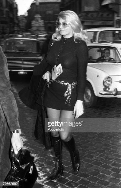 Rome Italy 23rd March 1971 Film actress Anita Ekberg wearing sunglasses a knitted mini dress and chain belt walks across the busy Piazza di Spagna