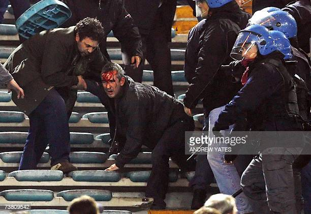 A Manchester United fan is hurt after being hit on the head during clashes with Italian riot policemen during their Champions League quarterfinal...
