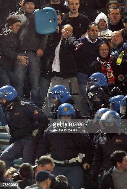 A Manchester United fan throws a seat during clashes with Italian riot policemen during their Champions League quarterfinal first leg football match...
