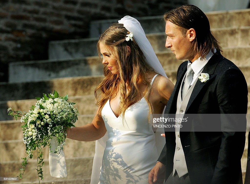 AS Roma captain Francesco Totti smiles to his wife Italian TV star Hilary Blasi leave the church after their wedding 19 June 2005 in Rome AFP...
