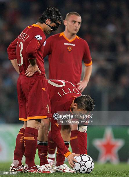 AS Roma's forward Francesco Totti prepares to shoot the ball flanked by defender Cristian Chivu and midfileder Daniele De Rossi during his team's...