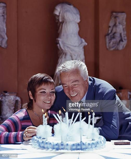 Rome Italy Italian movie director Vittorio de Sica and actress Gabriella Pallotta prepare to blow off the candles of the birthday cake for Vittorio's...