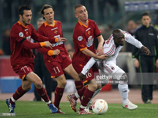 Milan's dutch midfielder Clarence Seedorf fights with three Rome players Daniele De Rossi Brazilian Taddei and Marco Cassetti during their Italian...