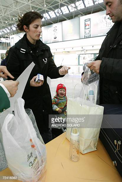 Passengers pack baby's items in a plastic bag 06 November 2006 at Rome Fiumicino Airport as new EUwide hand luggage rules came into force The new...