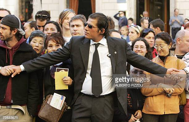 Private security keeps back fans of Hollywood superstar Tom Cruise waiting in front of a central Rome hotel where Cruise and his fiancee Katie Holmes...