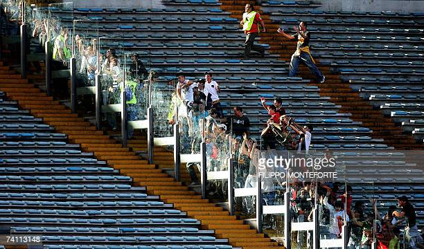 Roma's football club fans run to the glass that separates them from Inter Milan's supporters after their team scored during the Coppa Italia first...