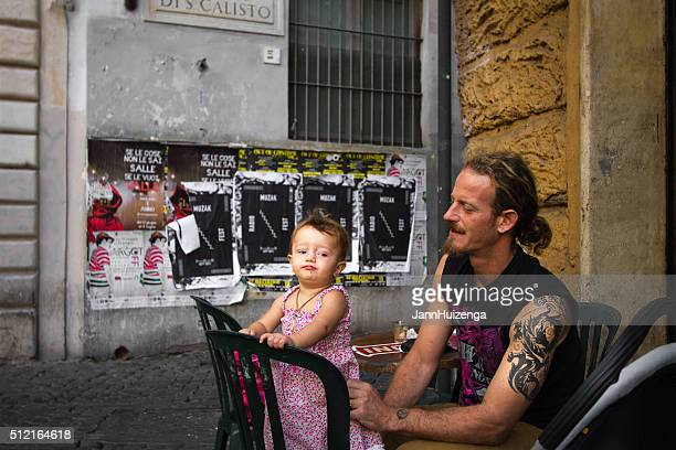 Rome, Italy: Tattooed Father and Baby Daughter at Outdoor Cafe