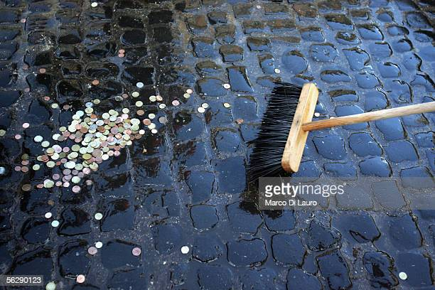 Rome Municipality employee collects the coins at the Trevi Fountain November 28 2005 in Rome Italy Tourists from all over the world come to Rome's...
