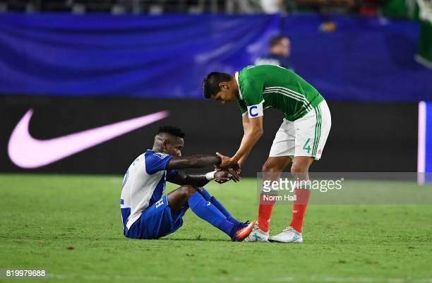Romell Quioto of Honduras is helped off the ground by Hugo Ayala of Mexico after losing 10 in a quarterfinal match during the CONCACAF Gold Cup at...