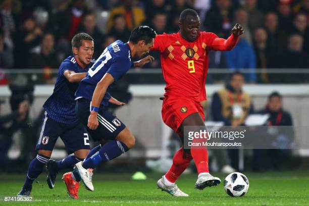 Romelu Lukaku of Belgium battles for the ball with Yosuke Ideguchi and Tomoaki Makino of Japan during the international friendly match between...