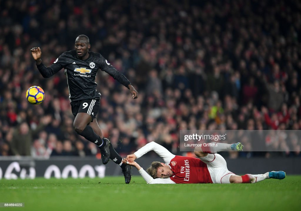 Romelu Lukaku of Manchester United gets tho the ball ahead of Nacho Monreal of Arsenal during the Premier League match between Arsenal and Manchester United at Emirates Stadium on December 2, 2017 in London, England.
