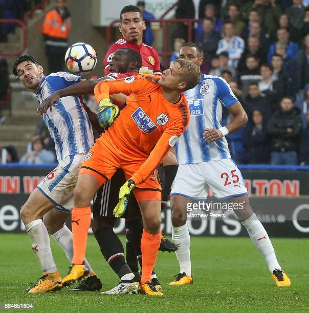 Romelu Lukaku of Manchester United in action with Christopher Schindler and Jonas Lossi of Huddersfield Town during the Premier League match between...