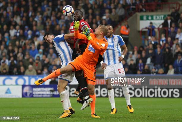Romelu Lukaku of Manchester United jumps with Jonas Lossl and Christopher Schindler of Huddersfield Town during the Premier League match between...