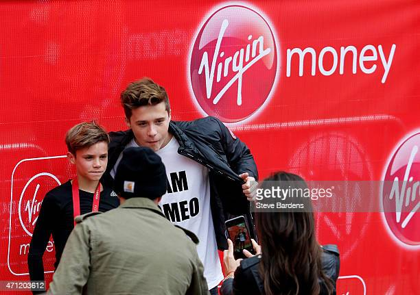 Romeo Beckham poses for a photo with his brother Brooklyn Beckham after taking part in the junior marathon during the Virgin Money London Marathon on...