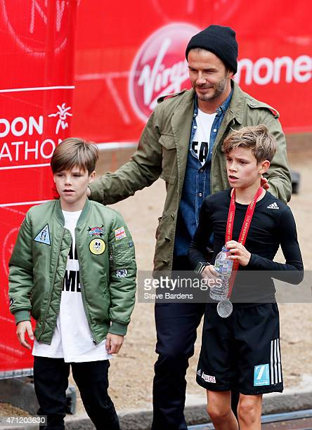 Romeo Beckham receives the support of his brother Cruz Beckham and father David Beckham after taking part in the junior marathon During the Virgin...