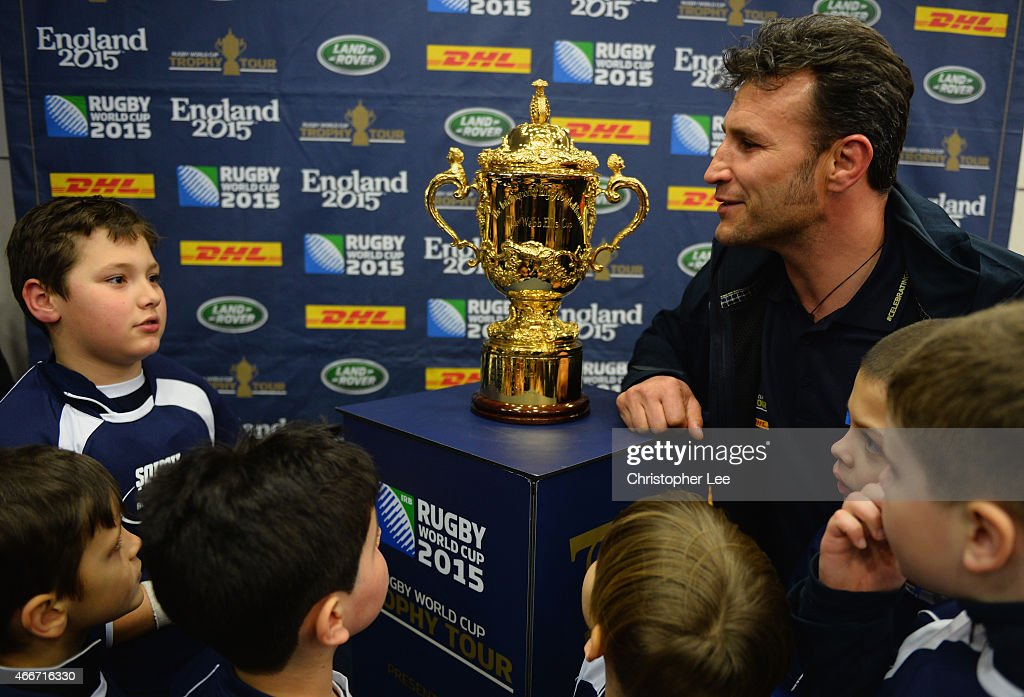 Romeo Gontineac talks to young rugby fans as they have their photograph taken with the Webb Ellis Cup during the Rugby World Cup Trophy Tour in partnership with Land Rover and DHL ahead of Rugby World Cup 2015 on March 17, 2015 in Bucharest, Romania.