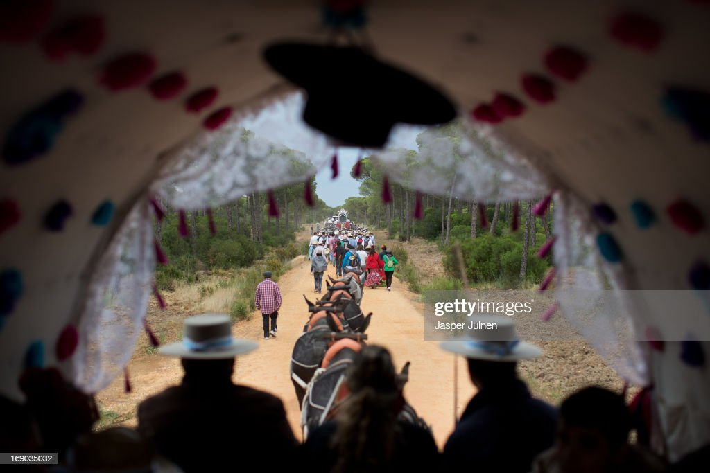 Romeros follow in their carriage behind Pilgrims walking behind the carriage carrying the Simpecado of the Hermandad del Rocio de Huelva during their journey to La Ermita del Rocio on May 16, 2013 in Huelva, Spain. The Romeria del Rocio procession brings together roughly a million pilgrims each year making their way for as long as seven days from throughout Andalusia by foot, on horsebacks and horse drawn carriages, to the doors of the Hermitage of El Rocio. On Sunday night, after reciting the Holy Rosary at candlelight, and the passing of all the simpecados in front of the chapel, with the one from the brotherhood of Matriz de Almonte as the last one, el salto de la reja begins, the jumping of the fence surrounding the Hermitage after which the Virgin of El Rocio is carried out onto the sandy streets of the small town for the 'Blanca Paloma' procession. Then, the long camino home begins. Dating back from 1653, it was in 1758, when the Virgin of Las Rocinas became known as the Virgin of El Rocio, that the pilgrimage started to take place in the weekend of the Sunday of Pentecost, 50 days after Easter Sunday.