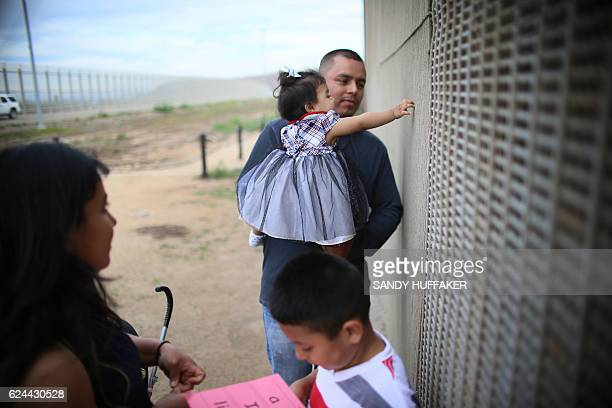 Romina Camacho 1 year touches the border fence while her father Armando holds her while visiting family members along the United StatesMexico Border...