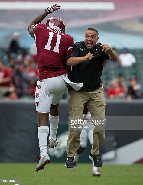 Romond Deloatch of the Temple Owls celebrates with head coach Matt Rhule at the end of the first half against the Charlotte 49ers at Lincoln...