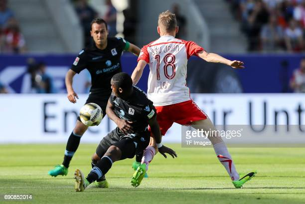 Romuald Lacazette of 1860 Munich und Marc Lais of Jahn Regensburg battle for the ball during the Second Bundesliga Playoff first leg match between...