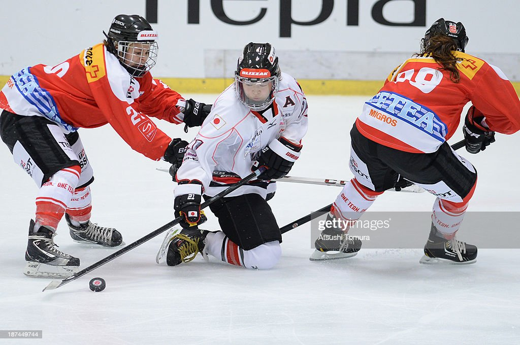 Romy Eggimann of Switzerland, Hanae Kubo of Japan and Karin Williner of Switzerland in action in the match between Japan and Switzerland during day three of the Ice Hockey Women's 5 Nations Tournament at the Shin Yokohama Skate Center on November 9, 2013 in Yokohama, Japan.