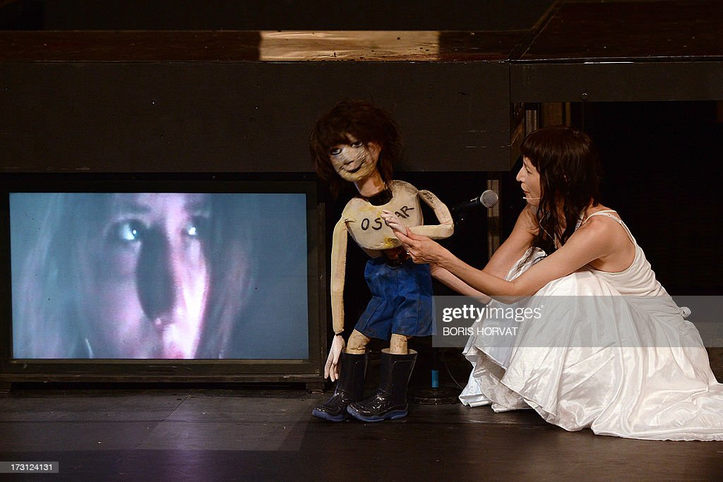 Romy Louise Lauwers (on screen) and Grace Ellen Barkey perform a play written and directed Belgian Jan Lauwers 'Place du marché 76' on July 7, 2013 in Avignon, during the 67th International Theatre festival.