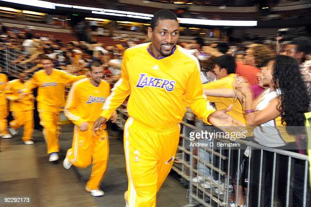 Ron Artest of the Los Angeles Lakers highfives a fan as he takes the court before the game against the Denver Nuggets on October 22 2009 at Honda...