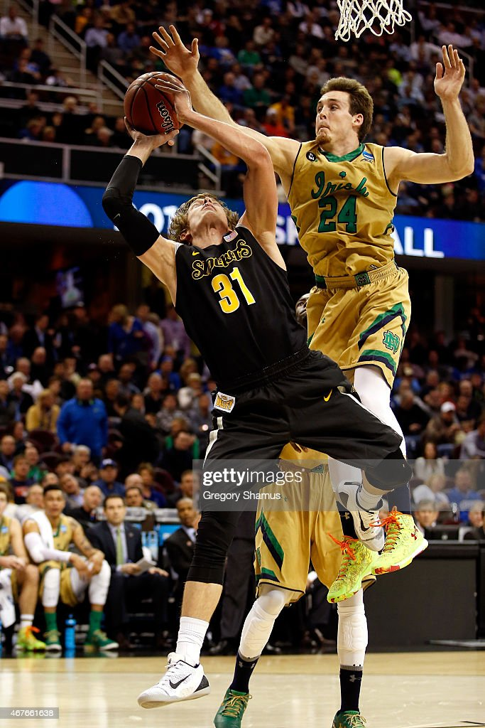 Ron Baker of the Wichita State Shockers drives to the basket against Pat Connaughton of the Notre Dame Fighting Irish in the first half during the...