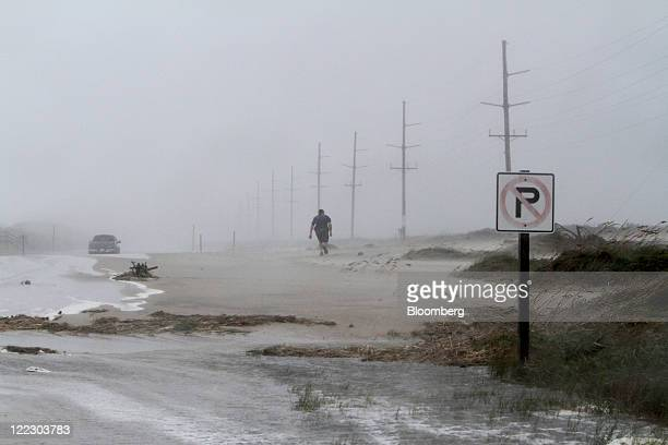 Ron Brietharp walks into a headwind to rescue his fiance's truck that got stuck in the sand and water covering NC 12 near Hatteras Village North...