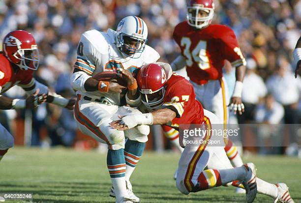 Ron Davenport of the Miami Dolphins gets tackled by Deron Cherry and Scott Radecic of the Kansas City Chiefs during an NFL football game September 22...