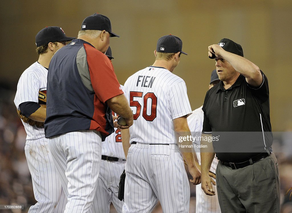Ron Gardenhire #35 of the Minnesota Twins speaks with second base umpire Gary Darling #37 as Casey Fien #50 of the Minnesota Twins returns to the bullpen during the eighth inning of the game against the Philadelphia Phillies on June 11, 2013 at Target Field in Minneapolis, Minnesota. The Twins defeated the Phillies 3-2.