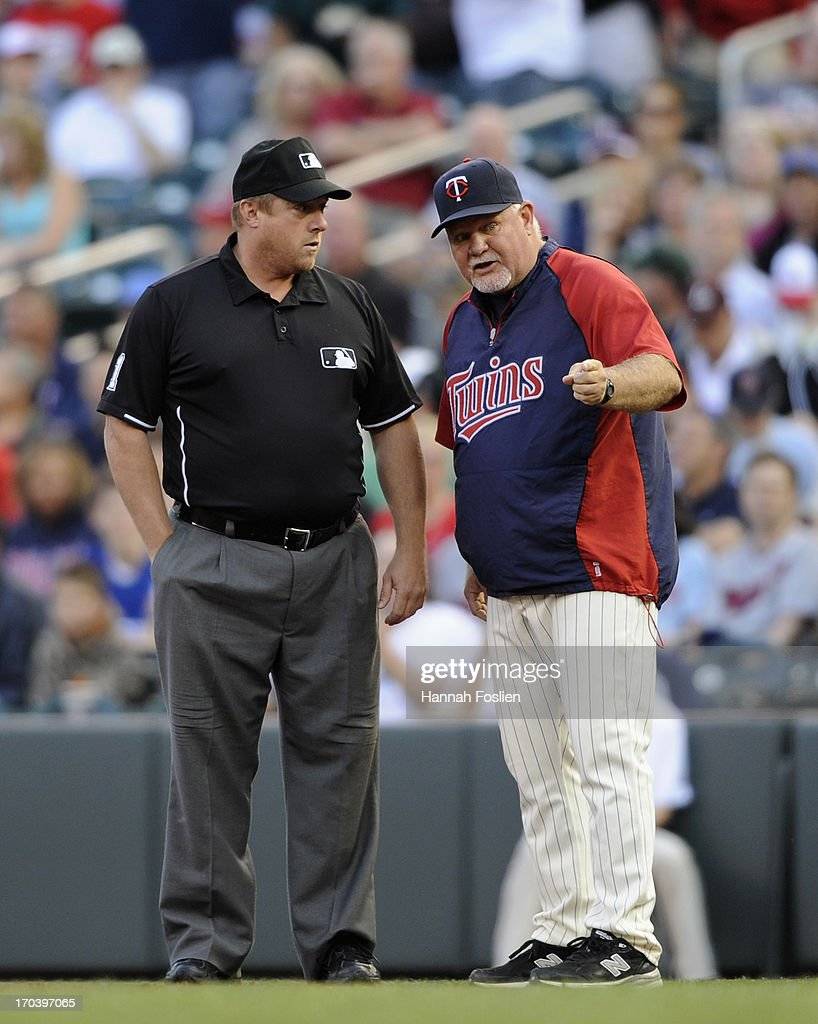Ron Gardenhire #35 of the Minnesota Twins speaks with umpire Bruce Dreckman #1 after Ben Revere #2 of the Philadelphia Phillies is called safe at first base during the first inning of the game on June 12, 2013 at Target Field in Minneapolis, Minnesota.