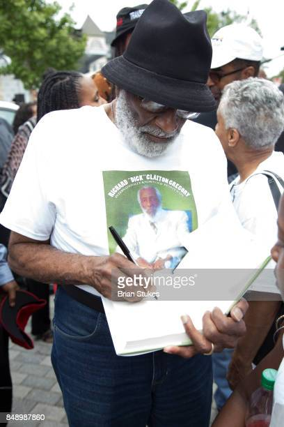 Ron Gregory signs copy of Dick Gregory's book 'Defining Moments in Black History Reading Between The Lies' during Dick Gregory's Parade Of Life at...