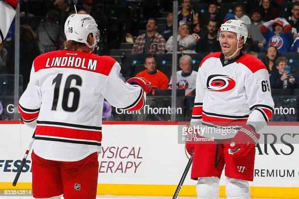 Ron Hainsey is congratulated by his teammate Elias Lindholm of the Carolina Hurricanes after scoring a second period goal against the New York...