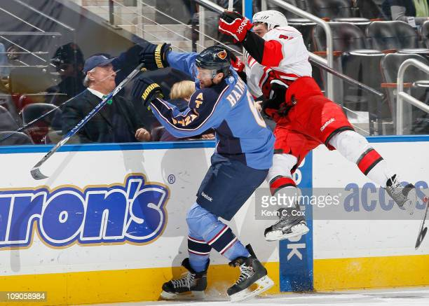 Ron Hainsey of the Atlanta Thrashers checks Jerome Samson of the Carolina Hurricanes into the boards at Philips Arena on February 13 2011 in Atlanta...