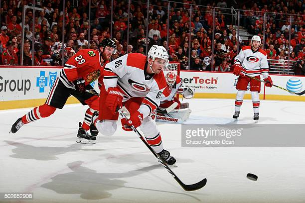 Ron Hainsey of the Carolina Hurricanes and Bryan Bickell of the Chicago Blackhawks chase the puck in the second period of the NHL game at the United...