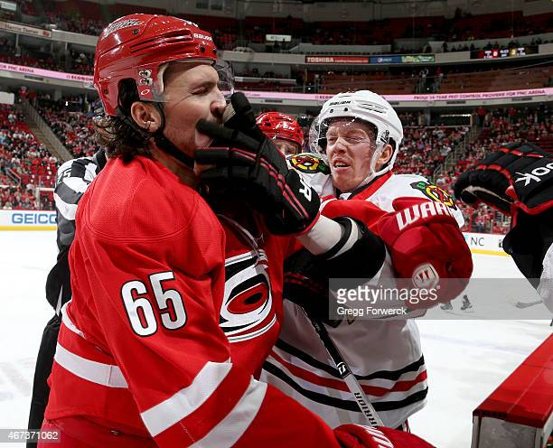 Ron Hainsey of the Carolina Hurricanes and Joakim Nordstrom of the Chicago Blackhawks fight near the bench during their NHL game at PNC Arena on...