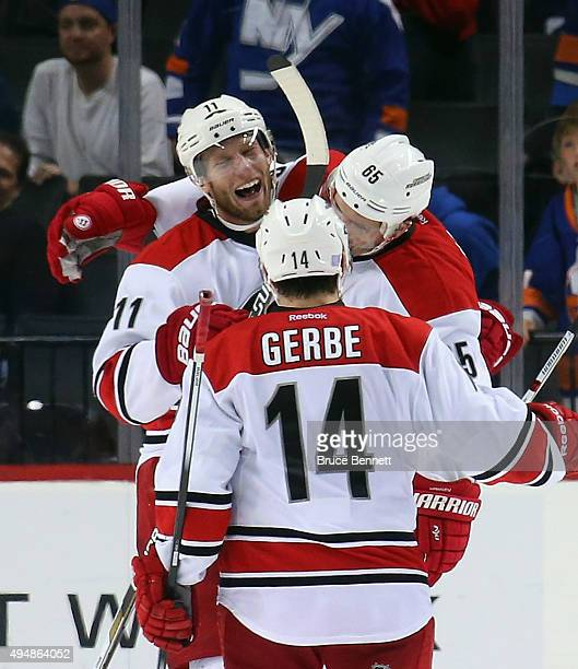 Ron Hainsey of the Carolina Hurricanes celebrates his game winning goal at 221 of the overtime against the New York Islanders along with Jordan Staal...