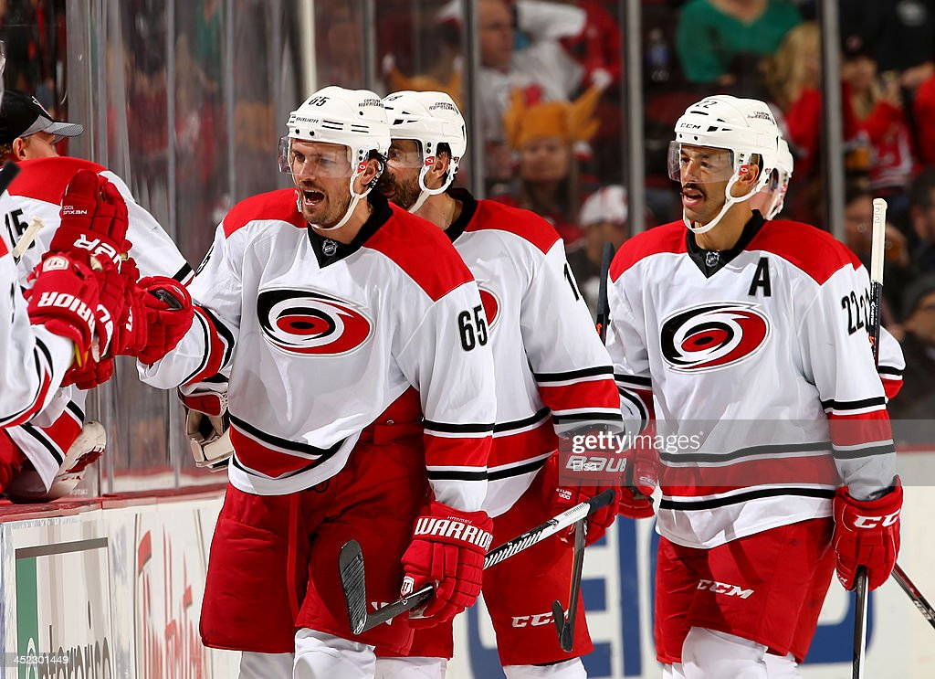 Ron Hainsey #65 of the Carolina Hurricanes celebrates his goal with teammates on the bench in the second period against the New Jersey Devils at Prudential Center on November 27, 2013 in Newark, New Jersey.