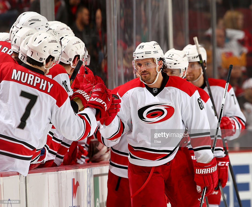 <a gi-track='captionPersonalityLinkClicked' href=/galleries/search?phrase=Ron+Hainsey&family=editorial&specificpeople=206345 ng-click='$event.stopPropagation()'>Ron Hainsey</a> #65 of the Carolina Hurricanes celebrates with teammates on the bench in the first period against the New Jersey Devils at Prudential Center on November 27, 2013 in Newark, New Jersey.