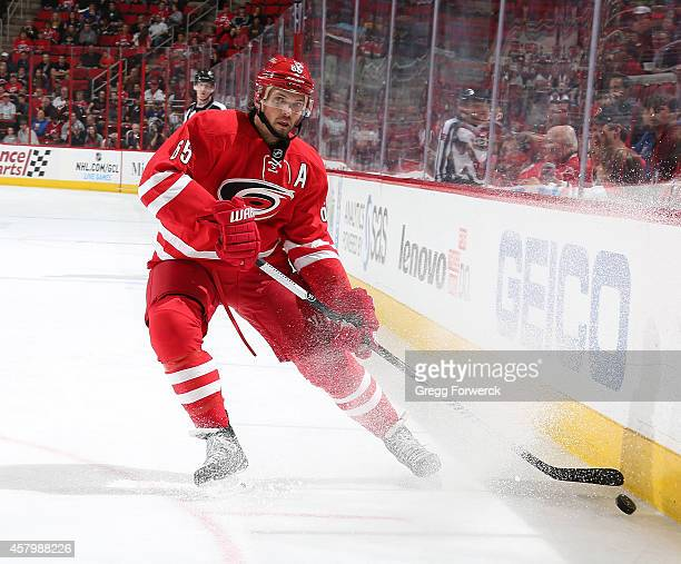 Ron Hainsey of the Carolina Hurricanes controls the puck along the boards during their NHL game against the Buffalo Sabres at PNC Arena on October 14...