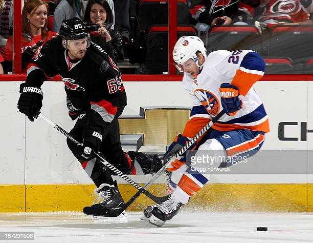 Ron Hainsey of the Carolina Hurricanes knocks the puck away from Thomas Vanek of the New York Islanders during their NHL game at PNC Arena on...