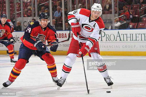 Ron Hainsey of the Carolina Hurricanes skates with the puck against Tomas Fleischmann of the Florida Panthers at the BBT Center on November 26 2014...