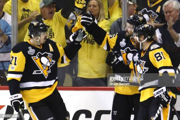 Ron Hainsey of the Pittsburgh Penguins celebrates with Evgeni Malkin and Phil Kessel after scoring his team's sixth goal against the Nashville...