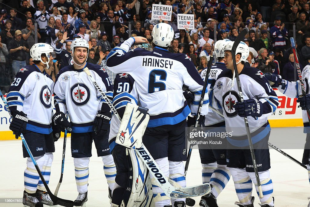 <a gi-track='captionPersonalityLinkClicked' href=/galleries/search?phrase=Ron+Hainsey&family=editorial&specificpeople=206345 ng-click='$event.stopPropagation()'>Ron Hainsey</a> #6 of the Winnipeg Jets congratulates goaltender <a gi-track='captionPersonalityLinkClicked' href=/galleries/search?phrase=Chris+Mason+-+Ice+Hockey+Player&family=editorial&specificpeople=171262 ng-click='$event.stopPropagation()'>Chris Mason</a> #50 as he and other members of the Jets celebrate a 5-3 victory over the Anaheim Ducks at the MTS Centre on December 17, 2011 in Winnipeg, Manitoba, Canada.