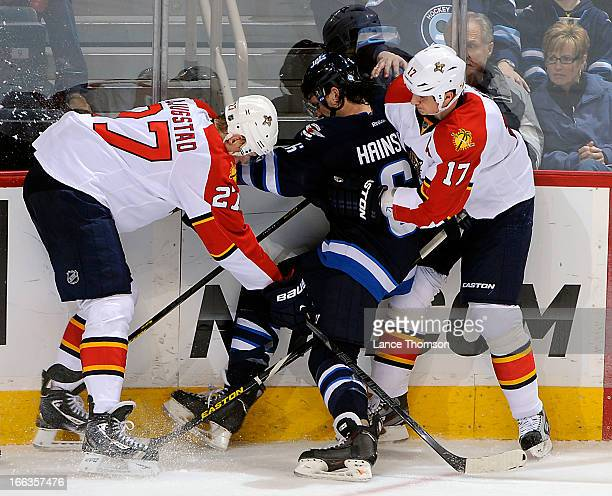 Ron Hainsey of the Winnipeg Jets gets sandwiched between Nick Bjugstad and Filip Kuba of the Florida Panthers as they battle along the boards during...