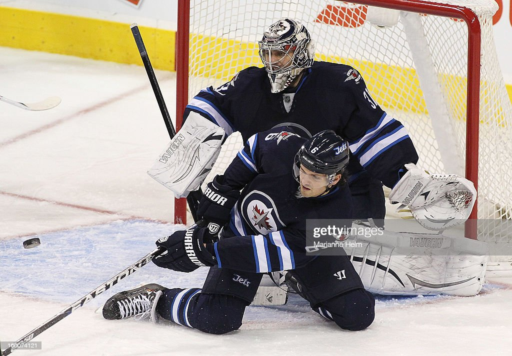 Ron Hainsey #6 of the Winnipeg Jets helps goaltender Ondrej Pavelec #31 block a shot on goal during a game against the Pittsburgh Penguins in NHL action on January 25, 2013 at the MTS Centre in Winnipeg, Manitoba, Canada.